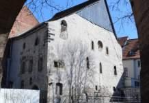 Die Alte Synagoge von der Waagegasse aus gesehen. Im Vordergrund des Fotos der steinerne Torbogen, der auf das Nachbargrundstück führt, von der Synagoge sieht man die Nord- und die Westfassade.