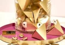 Ein Glas mit gefalteten goldenen Dreiecken auf einem Tablet. .
