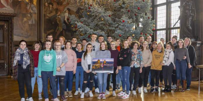Jugendliche stehen in einem festlichen Saal vor einem Weihnachtsbaum.