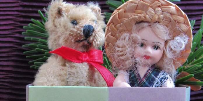 Puppe und Teddy in gebastelter Schachtel.