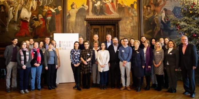 Menschen stehen für ein Gruppenfoto formatiert vor einer mit Gemälden verzierten Wand.