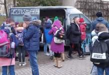 Kinder und Jugendliche auf einem Schulhof, dahinter ein Fahrzeug.