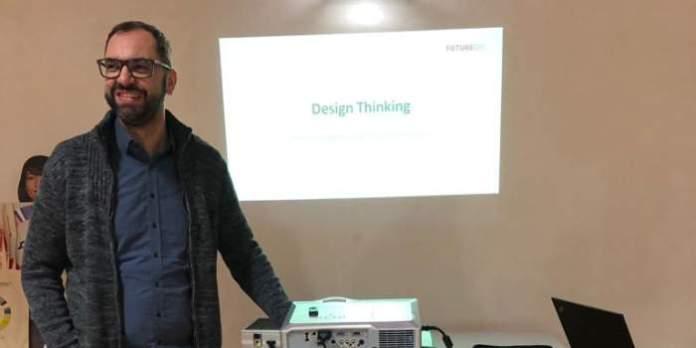 """Ein Referent steht am Beamer und hinter ihm auf der Power-Point-Präsentation steht """"Design Thinking""""."""