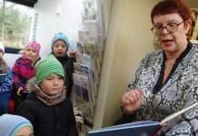 Frau liest Kindern aus einem Buch vor.