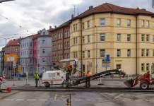 eine Straßenbauestelle mit Baumaschinen und einer Häuserzeile im Hintergrund