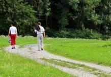 Ein Paar unterwegs auf einem Wiesenweg.