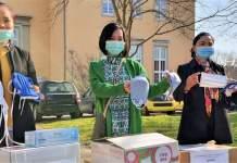 Drei Frauen mit einer Schutzmaske im Gesicht halten selbstgenähte Schutzmasken in ihren Händen