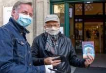 Zwei Männer mit Masken vor dem Eingang zur Bibliothek.