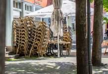 Zwischen einer Reihe junger Bäume in der Stadt stehen übereinander gesteckte Stühle vor einem Restaurant.