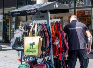 ein Mitarbeiter der Ordnungsbehörde schiebt einen Warenständer mit Rucksäcken und Taschen
