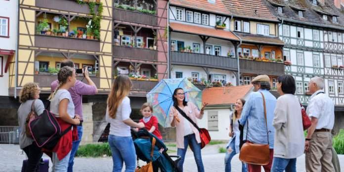 Eine Gruppe von Menschen ist einer jungen Frau mit Namensschild zugewandt und hört ihr zu, während im Hintergrund viele alte Fachwerkhäuser mit Balkonen zur Krämerbrücke aneinandergereiht sind.