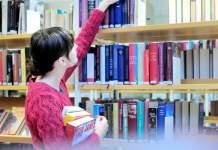 Ein junges Mädchen mit Büchern in der Hand vor einem Bücherregal.