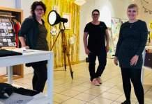 3 Personen stehen zwischen Ausstellungsregalen mit Waren in einem Ladenlokal.