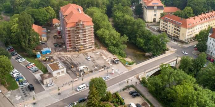 Eine Luftaufnahme mit einer Straße, einem eingerüsteten Schulgebäude und einem Schulhof, der noch gebaut wird.