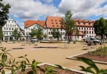 eine Parkanlage mit Beeten und großflächigen Wegen