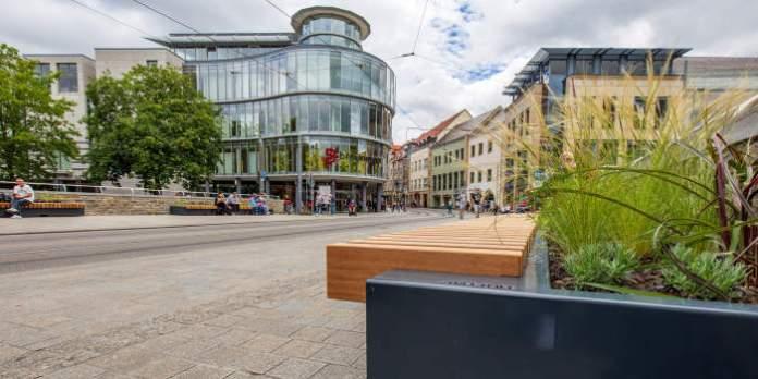 mit Bepflanzungen kombinierte Bänke stehen auf breiten Gehwegen entlang einer Straße in der Innenstadt