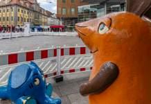 Die Kika-Figuren Maus und Elefant stehen auf einem großen Innenstadtplatz, hinter ihnen sind Bauzäune.