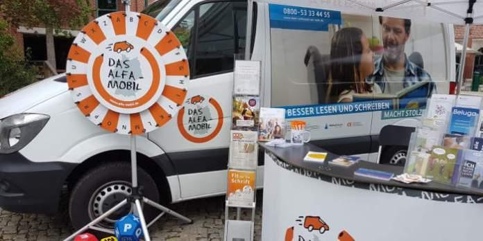 ein Infostand mit einem Transporter im Hintergrund, einem Glücksrad und verschiedenen Infomaterialien