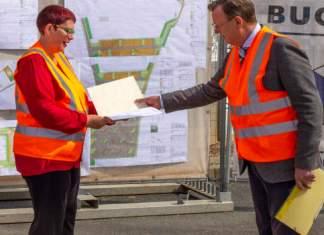 Ein Mann übergibt einer Frau eine Mappe, beide tragen orangefarbene Warnwesten,im Hintergrund sind Baupläne.