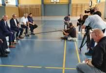 Fünf Politiker sitzen vor acht Fotografen