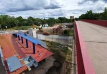 eine Baustelle, rechts eine bestehende Brücke, links liegen die Teile für den Neubau