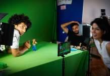 Drei Menschen stehen in einem Filmset, betstehend aus Leinwand, Kamera und Beleuchtung.
