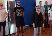 7 Personen stehen vor einer Pinnwand für ein Gruppenfoto mit Abstand nebeneinander aufgereiht.