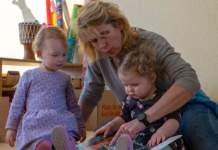 eine Frau sitzt mit zwei Kindern auf dem Boden und liest in einem Buch