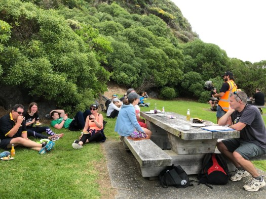 Photo of people sitting on grass and seats eating food