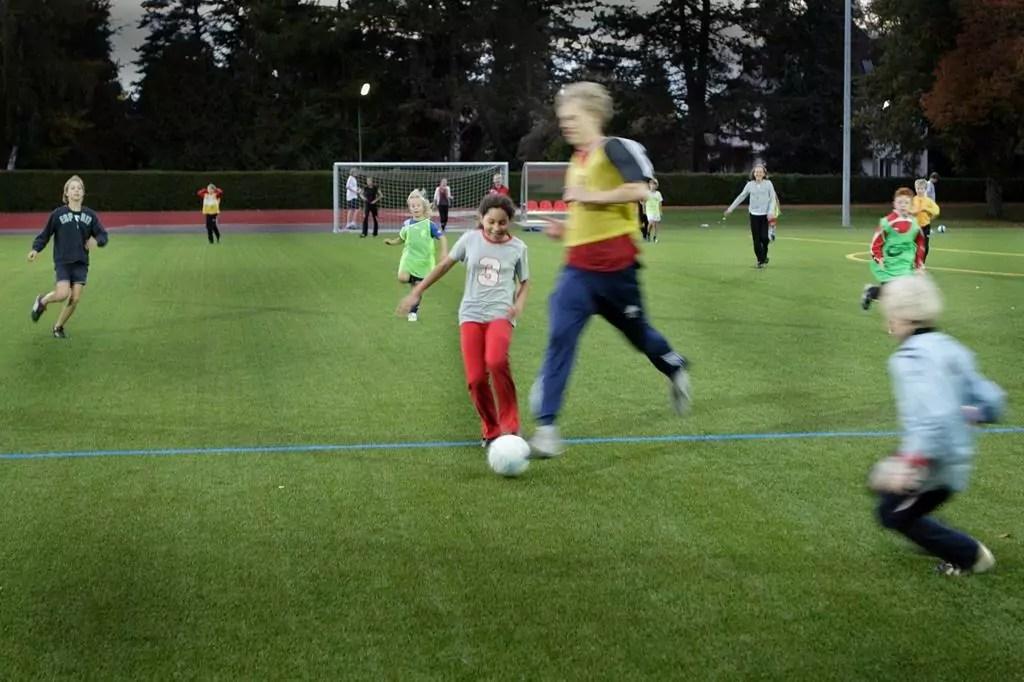 Kinder spielen auf dem Kunstrasenplatz Fußball
