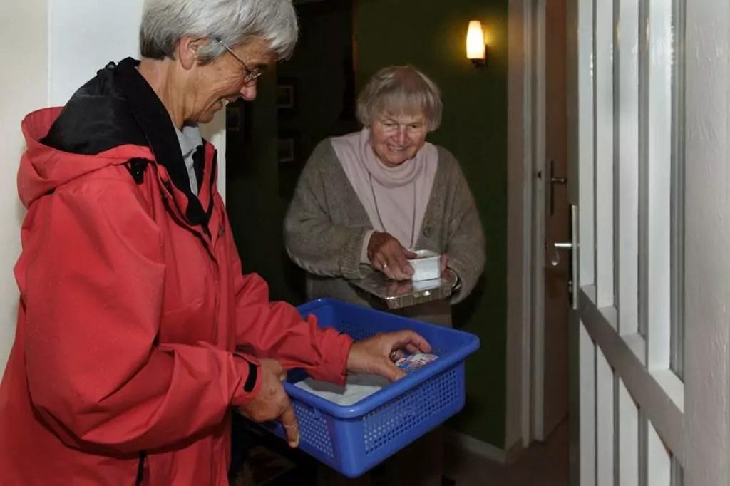 Alte Dame nimmt Essen an der Haustür entgegen
