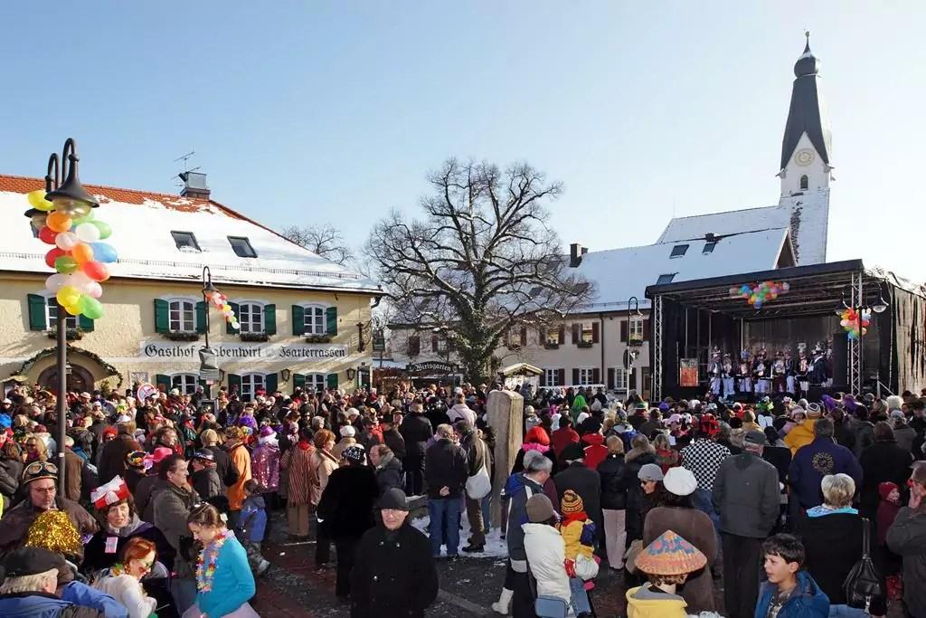"""Der Kirchplatz ist während der Faschingsfeier voller Menschen, verkleidet und unverkleidet. Die Sonne scheint. Auf der Bühne sind die """"D'Schwanecker Rittersleit"""" zu sehen"""