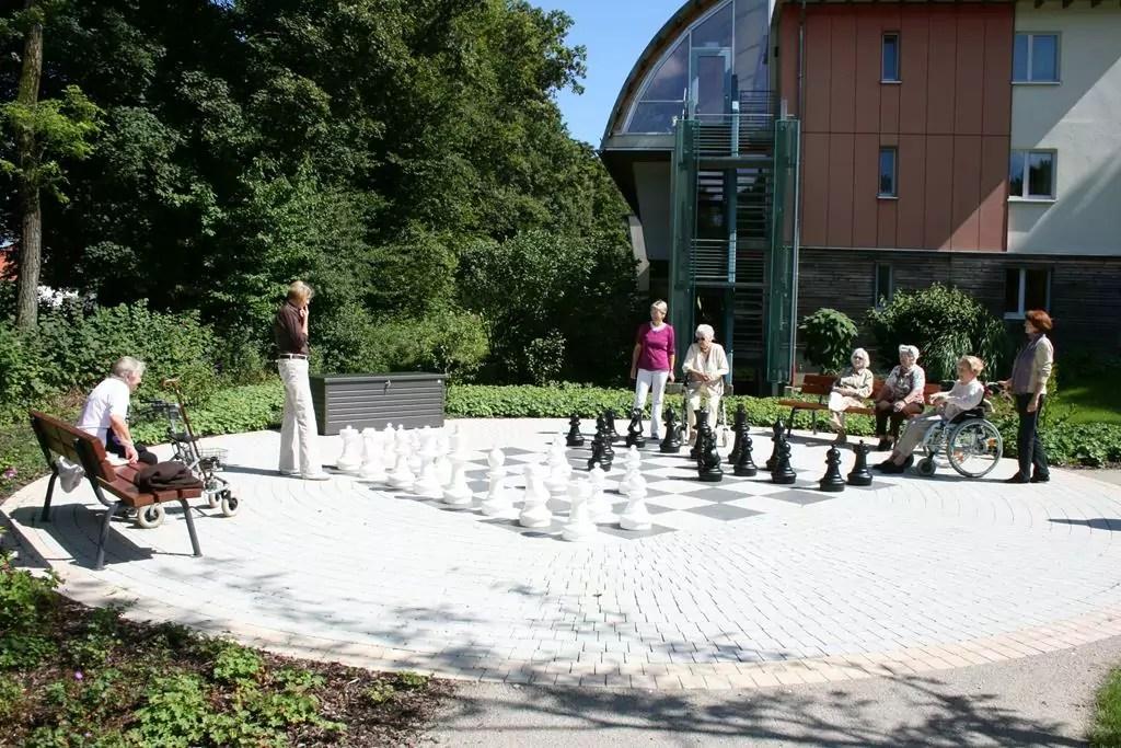 Senioren spielen Schach auf einem großen Schachbrett im Park des Hauses am Wiesenweg
