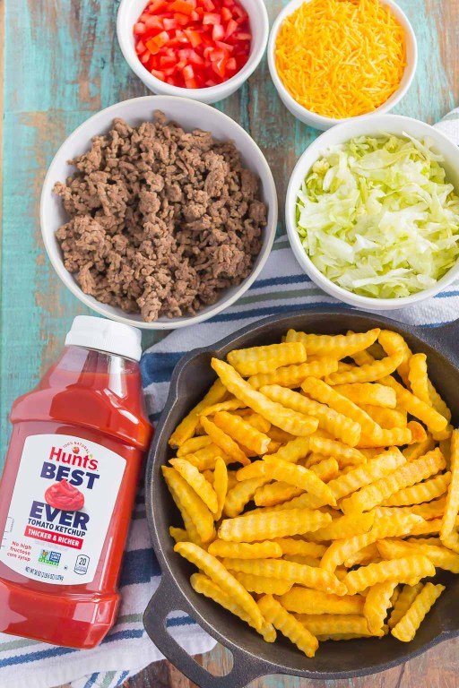 Loaded Cheeseburger Fries taste just like your favorite burger, but in appetizer form. These fries are topped with the classic ingredients of a cheeseburger and are baked to perfection. Easy to make and even better to eat, you'll love the crispy, crunchy, cheesy taste of this fun snack! #fries #cheeseburgerfries #loadedfries