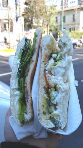 2 panini, la metà a sinistra acciughe, ricotta e misticanza, la metà a destra gamberoni, salsa yogur e zucchine