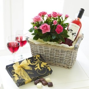 cestino con vino rosato, scatola con cioccolatini e un fascio di rose rosa