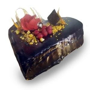 torta a forma di cuore al cioccolato con decori gialli e rosa rossa