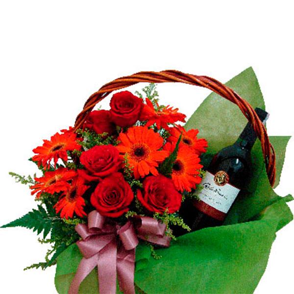 cestino con un bouquet di rose rosse e gerbere rosse e una bottiglia di vino rosso