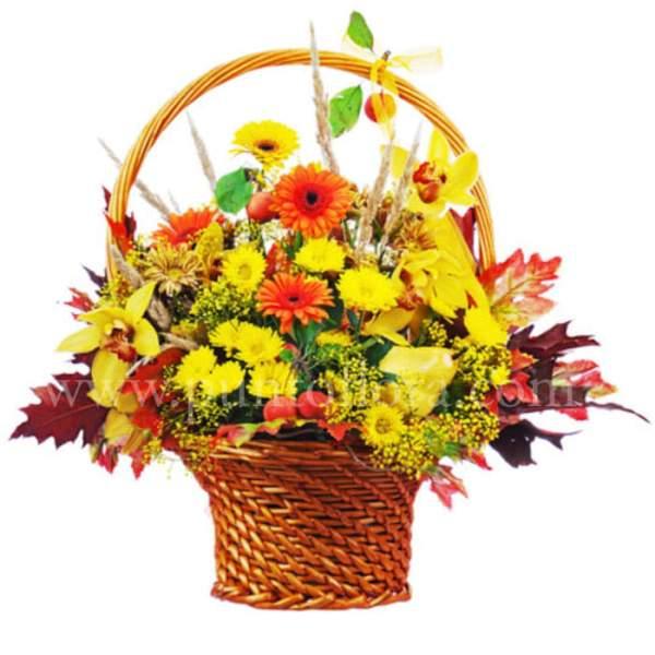 cesto in vimini con gerbere gialle, gerbere arancio, verde decorativo e foglie colorate.