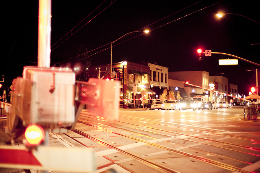 Pasadena train/ road intersection at night.