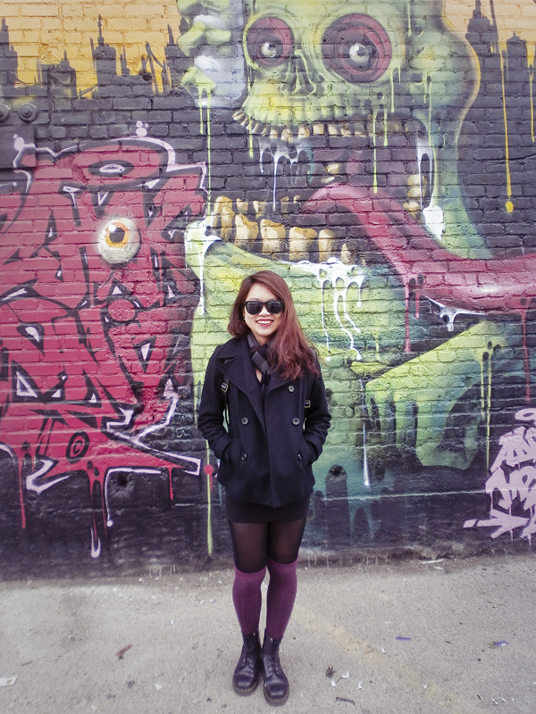 Jac in front of a wall of colourful murals.