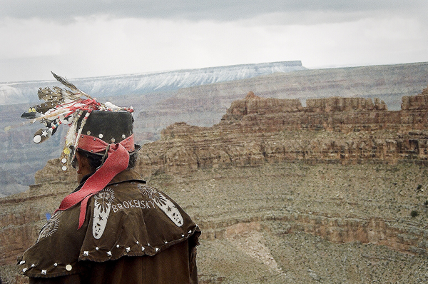 View of the Grand Canyon and of a tribal native.