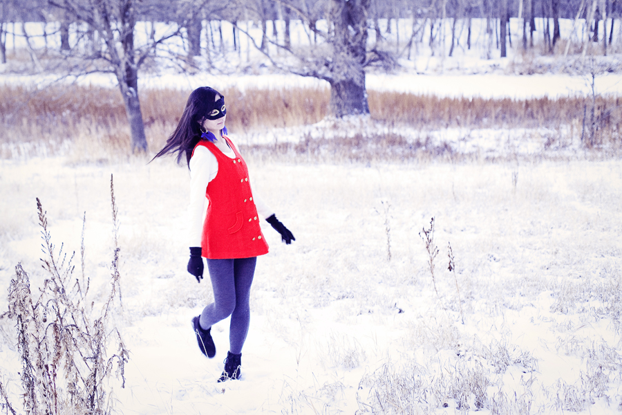 Self-portraiture photography in the snow- Feather masked red vest. Outfit details: gifted wool cape, thrifted red vest, Uniqlo cashmere sweater, River Island panda scarf, Forever21 knit tights, H&M blue feather hoop earrings, Fila boots.