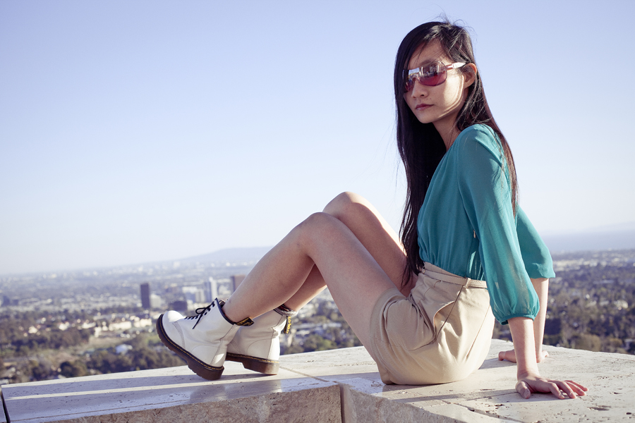 Perched on the ledge of the Getty Center. Outfit details: Forever21 chiffon green tan romper, La Marelle pink bow metal necklace, Uniqlo grey bra-top camisole, Dr. Martens white 8eye boots.