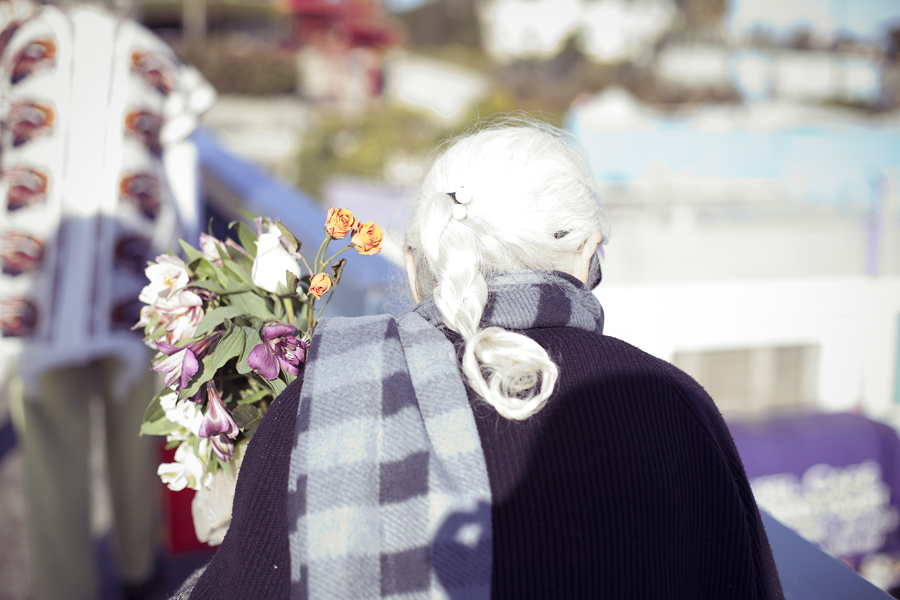 Old lady carrying a bouquet of flowers walking up Santa Monica pier.
