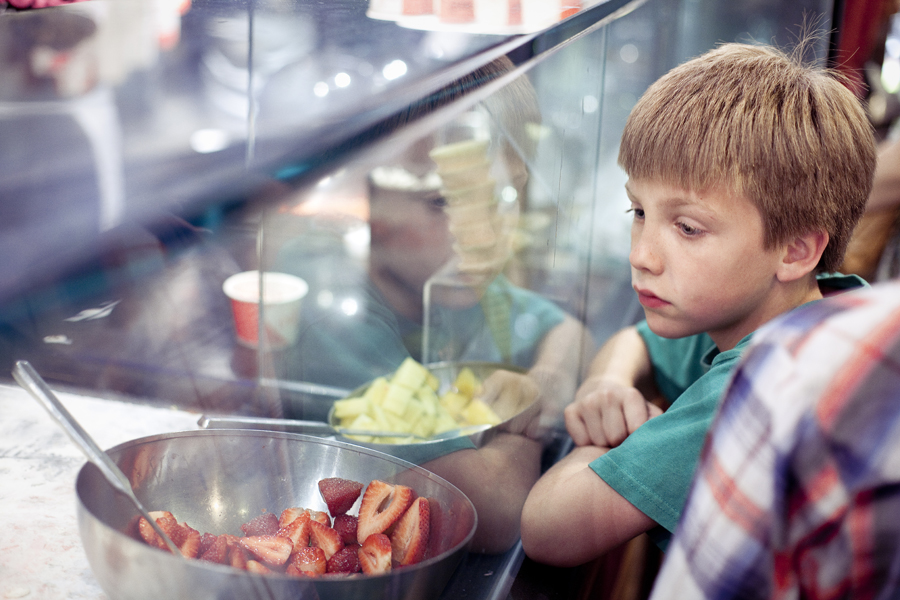 Boy looks on behind the glass pane as frozen yogurt is being made at 21 Choices in Pasadena.