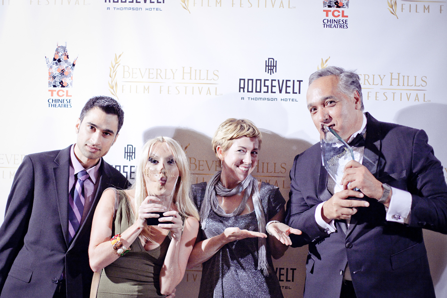 Kissing the awards in front of the backdrop at the Beverly Hills Film Festival awards ceremony at the Four Seasons Hotel.