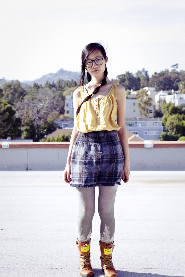 Rooftop self portrait. Composited photo. Outfit of the Day: Forever 21 yellow sleeveless top, Urban Outfitters printed tights, Top Shoes brown boots, Zara navy plaid wool skirt, black rimmed hipster glasses.