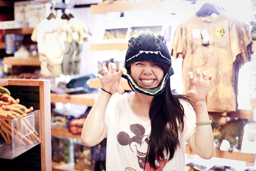 Lilli trying on a dinosaur hat at the souvenir shop in Natural History Museum in Los Angeles.