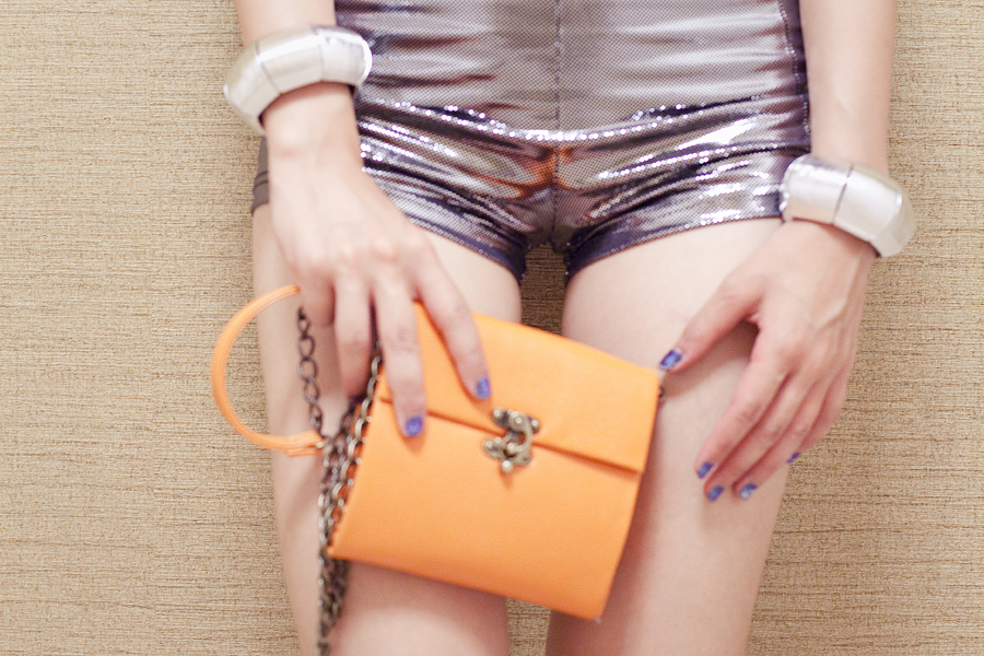 Close-up of outfit of the day: Forever 21 silver hot shorts, Cotton On silver bangles, Steve Madden orange sling bag.